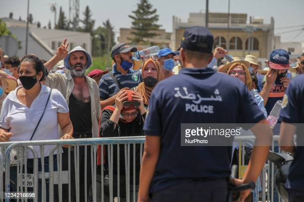 Supporters of the Islamist party Ennahdha stand in front of members of the riot police, during a sit-in protest led by the Tunisian Parliament...