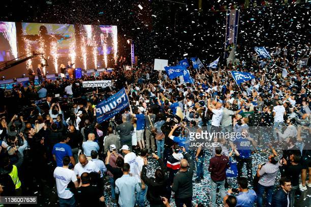 Supporters of the Israeli Likud Party celebrate as Prime Minister Benjamin Netanyahu waves to them at its headquarters in the Israeli coastal city of...