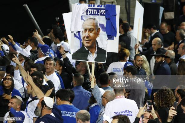 Supporters of the Israeli Likud Party wave party and national flags along with a sign showing Prime Minister Benjamin Netanyahu as they gather at its...
