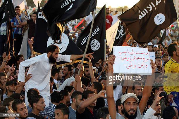 Supporters of the Jihadist group Ansar alSharia shout religious slogans while holding AlQaedaaffiliated flags to counter a demonstration by thousands...