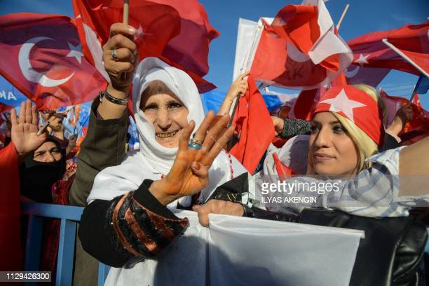 Supporters of the Justice and Development Party wave Turkish national flags during a local election rally with the Turkish President in Diyarbakir...