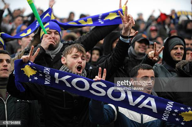 Supporters of the Kosovo team holding scarves reading 'Kosovo' cheer in the stands during the friendly football match between Kosovo and Haiti on...