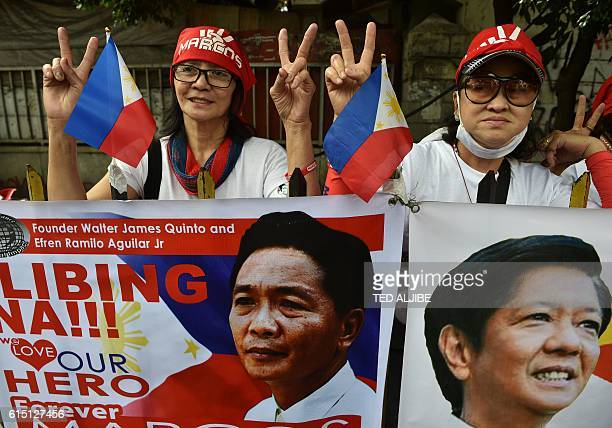 Supporters of the late dictator Ferdinand Marcos flash the V sign behind portraits of Marcos and his son former senator Bongbong Marcos at the start...