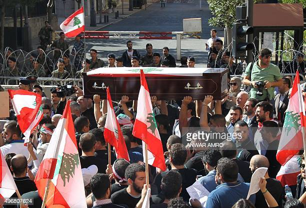 Supporters of the Lebanese Christian Phalange party carry an empty coffin symbolizing the Constitution of Lebanon during a protest near the...