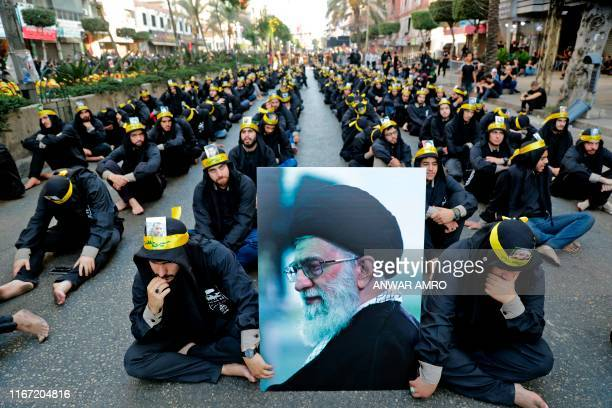 Supporters of the Lebanese Shiite Hezbollah movement hold a picture of Iran's Supreme Leader Ayatollah Ali Khamenei as they take part in a religious...