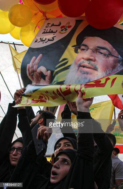 Supporters of the Lebanese Shiite Hezbollah movement wave banners and a photograph of the movement's leader Hasan Nasrallah in the town of AlAin in...
