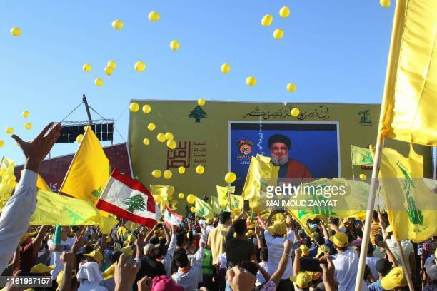 Supporters of the Lebanese Shiite militant movement Hezbollah wave th group's flag during a commemoration marking the 13th anniversary of the end of...
