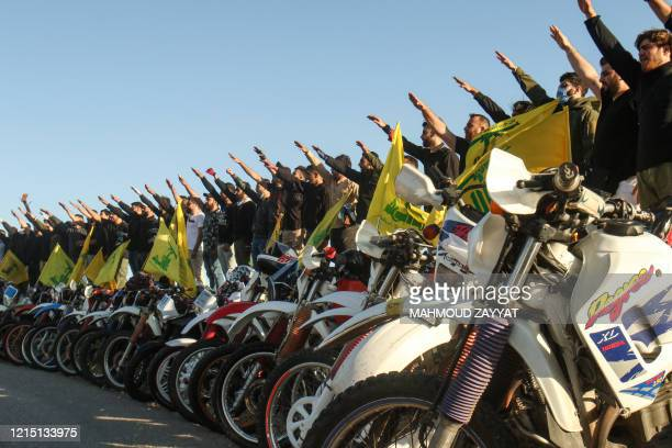 Supporters of the Lebanese Shiite movement Hezbollah perform a salute as they stand behind motorcycles carrying the group's flags in the southern...