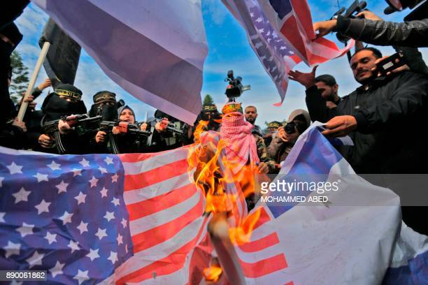 TOPSHOT Supporters of the militant Palestinian group Islamic Jihad burn US flags during a protest against US President Donald Trump's decision to...