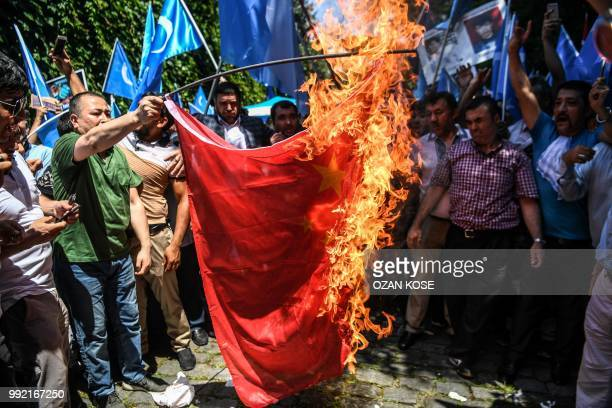 TOPSHOT Supporters of the mostly Muslim Uighur minority and Turkish nationalists burn a Chinese flag during a protest to denounce China's treatment...