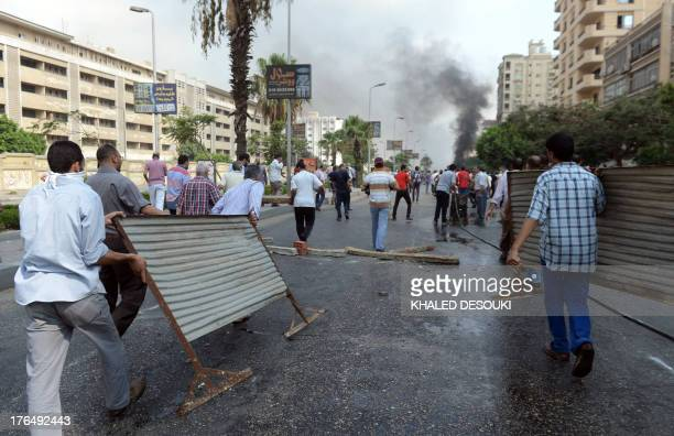Supporters of the Muslim Brotherhood and Egypt's ousted president Mohamed Morsi carry pieces of metal to try to barricade a road leading to the Rabaa...