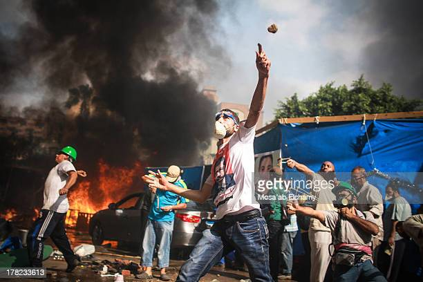 CONTENT] Supporters of the Muslim Brotherhood and Egypt's ousted president Mohamed Morsi throw stones during clashes with security forces in Cairo on...