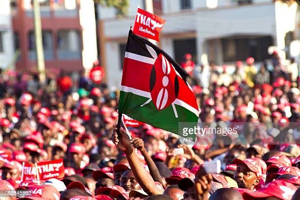 Supporters of The National Alliance presidential hopeful Uhuru Kenyatta wave a TNA flag as well as a Kenyan flag during a political rally held in the...