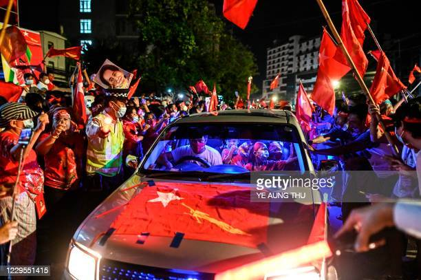 Supporters of the National League for Democracy party celebrate in front of the party's headquarters in Yangon on November 9 as NLD officials said...