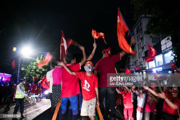 Supporters of the National League for Democracy party hold flags as they celebrate in front of the party's headquarters in Yangon on November 9 as...