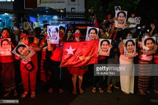 Supporters of the National League for Democracy party hold portraits of Aung San Suu Kyi as they celebrate in front of the party's headquarters in...