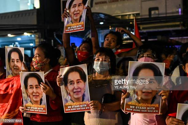 Supporters of the National League for Democracy party hold posters with the image of Myanmar state counsellor Aung San Suu Kyi as supporters...