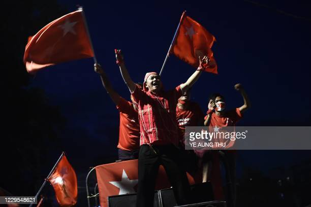 Supporters of the National League for Democracy party wave flags during celebrations in front of the party's headquarters in Yangon on November 9 as...