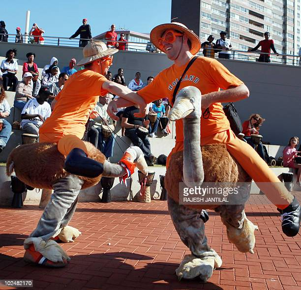Supporters of the Netherlands football team dressed in ostrich outfits dance to a drum session on Durban's North Pier beach prior to the 2010 World...