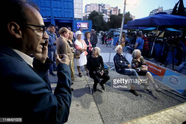 Supporters of the New Democracy party react as they watch the results of exit poll in an electoral kiosk in central Athens Greece on May 26 2019...
