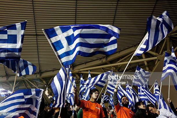 Supporters of the New Democracy party wave Greek and New Democracy party flags while Antonis Samaras Greece's prime minister not pictured speaks at...