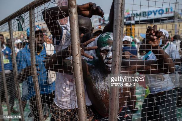 Supporters of the Nigeria's ruling party All Progressive Congress react as they breach the security barrier as President Muhammadu Buhari leaves the...