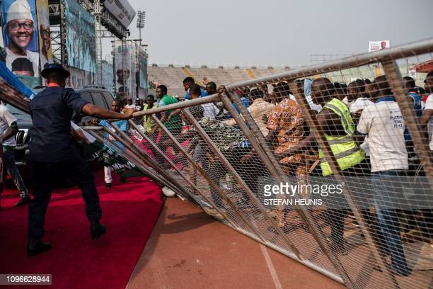Supporters of the Nigeria's ruling party All Progressive Congress breach the security barrier as President Muhammadu Buhari leaves the APC political...