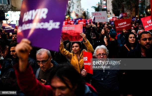 """Supporters of the """"No"""" gesture and chant slogans as they hold placards reading """"No"""" during a march at the Kadikoy district in Istanbul on April 17,..."""