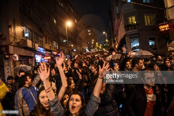 """Supporters of the """"No"""" gesture and shout as they gather at the Besiktas district in Istanbul on April 17, 2017 to protest following the results in a..."""