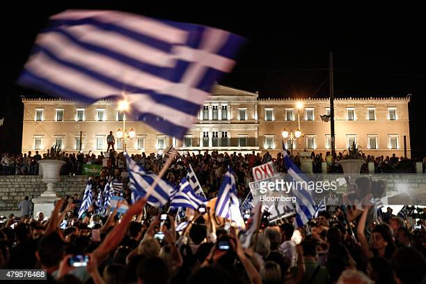Supporters of the 'No' vote wave Greek national flags outside the parliament after early results show the 'OXI' or 'No' vote ahead in the Greek...