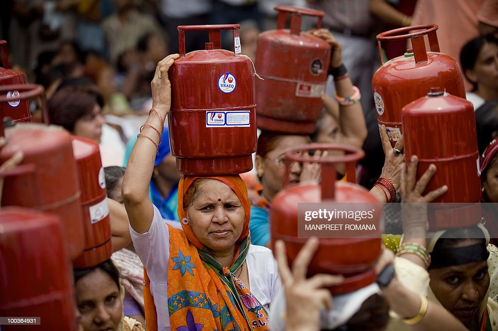 Supporters of the opposition Bharatiya Janata Party (BJP) carry cooking gas cylinders over their heads during a protest in New Delhi on May 24, 2010. Opposition BJP members and supporters held a sit-in protest in the nation's capital in observation of a 'black day' over the rising prices of essential commodities. AFP PHOTO/ Manpreet ROMANA