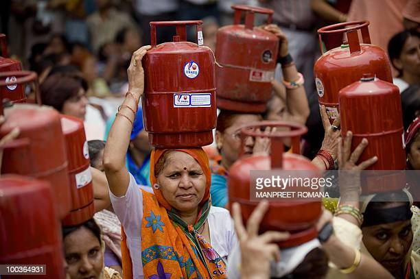 Supporters of the opposition Bharatiya Janata Party carry cooking gas cylinders over their heads during a protest in New Delhi on May 24 2010...