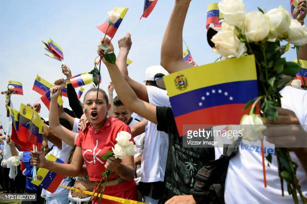 Supporters of the opposition chant as they wave a flags and hold white flowers during an attempt to enter humanitarian aid into Venezuela at Las...