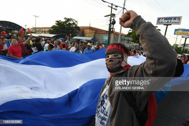TOPSHOT Supporters of the opposition Libertad y Refundacion party hold a protest within the anniversary of the reelection of President Juan Orlando...