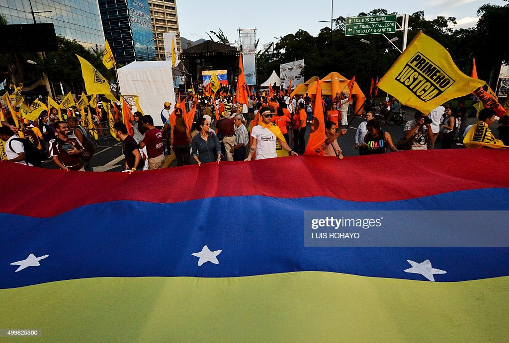 Supporters of the opposition Movement of Democratic Unity (MUD) party attend the campaign closing rally on December 3, 2015 in Caracas, Venezuela. Polls suggest the coalition that includes opposition leader Henrique Capriles' party could win a majority in the National Assembly for the first time since late socialist leader Hugo Chavez took power in 1999.