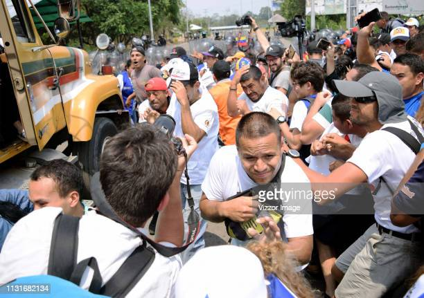 Supporters of the opposition run as Venezuelan security forces throw them tear gas during an attempt to enter humanitarian aid into Venezuela at the...