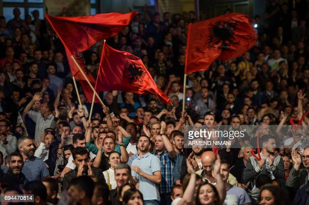 Supporters of the opposition Vetevendosje party wave Albanian national flags during the party's closing election campaign rally in Pristina on June 9...