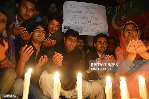 Supporters of the Pakistan TehreekeInsaaf party place candles to pay tribute to gunshot victim Malala Yousafzai in Islamabad on October 10 2012...