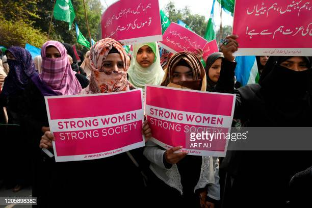Supporters of the Pakistani Islamic political party Jamaat-e-Islami hold placards as they march during a rally to mark the International Women's Day...