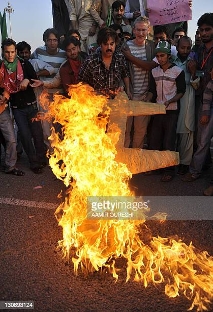 Supporters of the Pakistani politician Imran Khan and chief of Tehreek-e-Insaf party, burn a replica drone as they shout slogans during protest rally...