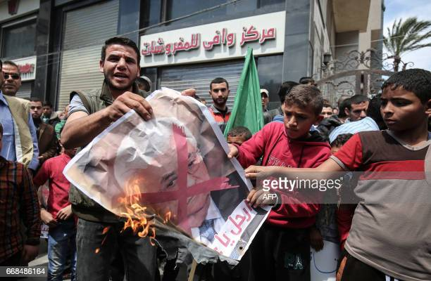 Supporters of the Palestinian Hamas movement burn a crossedout portrait of Palestinian leader Mahmud Abbas during a protest against the Israeli...
