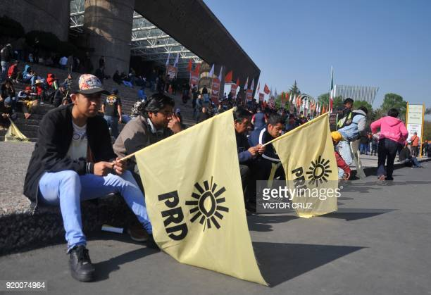 Supporters of the Party of the Democratic Revolution hold flags from their party as they arrive to protest against the presidential candidate of the...