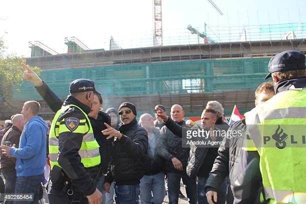 Supporters of the Pegida movement argue with the police officers as they stage protest in Utrecht The Netherlands on October 11 2015