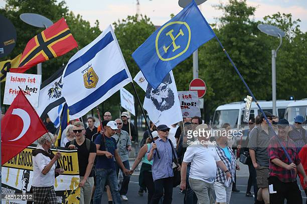 Supporters of the Pegida movement carry flags as they march past the Reichstag on August 24 2015 in Berlin Germany Pegida is critical of Islam and...