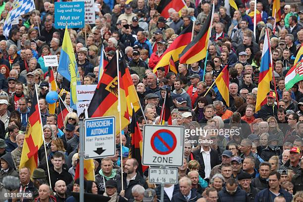 Supporters of the Pegida movement carrying German flags gather to march on German Unity Day on October 3 2016 in Dresden Germany Unity Day called Tag...
