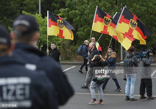 Supporters of the Pegida movement carrying German flags with the addition of a cross arrive to march on German Unity Day on October 3 2016 in Dresden...