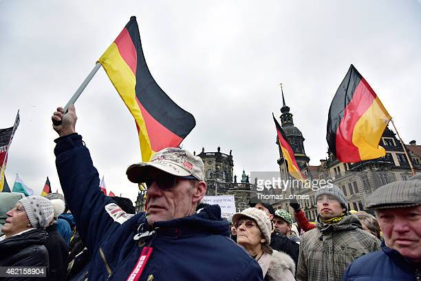 Supporters of the Pegida movement hold German flags during their weekly demonstration on January 25 2015 in Dresden Pegida is an acronym for...