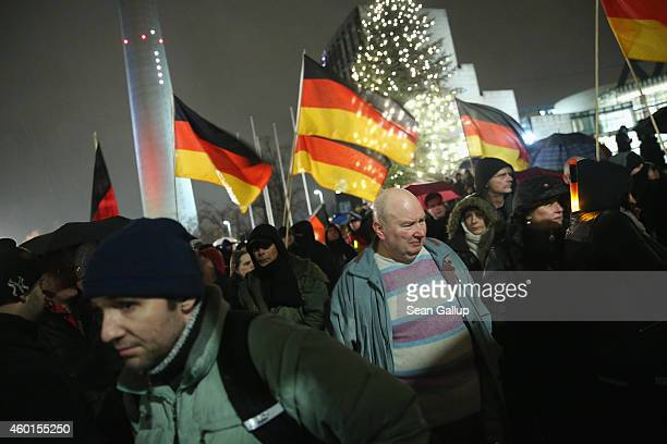 Supporters of the Pegida movement hold up German flags as they gather to protest on December 8 2014 in Duesseldorf Germany Pegida is an acronym for...