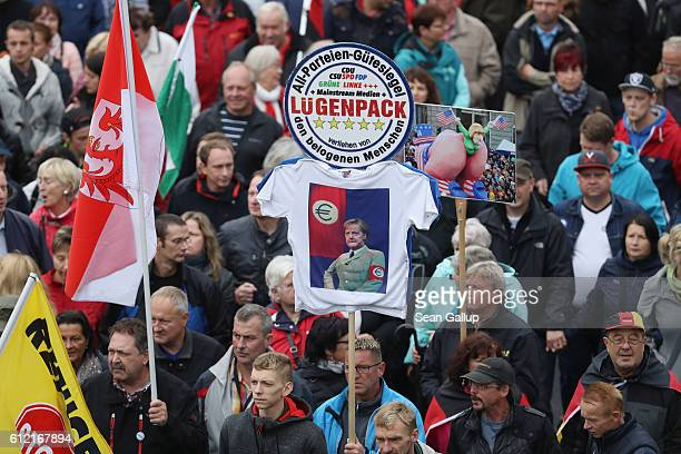 Supporters of the Pegida movement including one holding a sign that shows German Chancellor Angela Merkel dressed in a Nazi uniform with the...