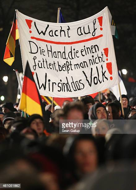 Supporters of the Pegida movement including some holding a sign that reads 'Wake Up Don't bite the hand that feeds you We are the people' gather for...